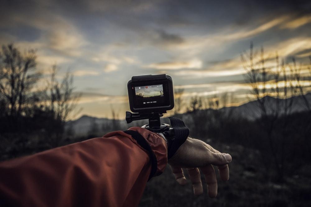 Een GoPro die op een hand gemonteerd is.