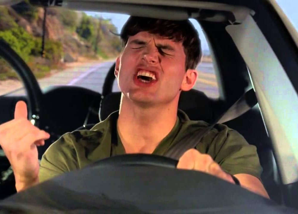 Man zingt mee met muziek in de auto