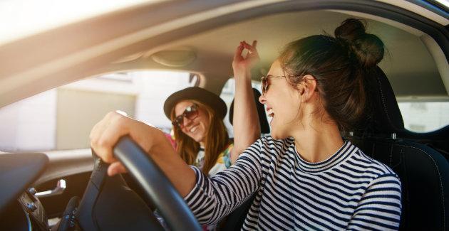 Mensen zingen onderweg mee met de muziek in de auto